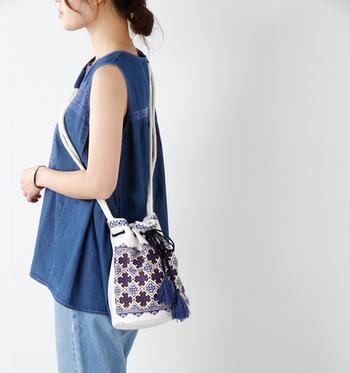 ボヘミアンテイストを感じさせるタッセル付きの巾着型ショルダーバック。エスニックな幾何学模様の刺繍の手作り感が素敵です。
