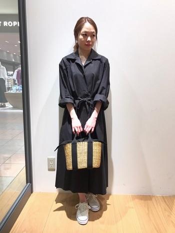 AURALEEのロングシャツドレスはゆったりめの袖口をロールアップして、上品なカジュアルテイストになりました。同色系のラインが入ったカゴバッグがよく似合っています。