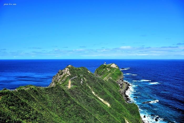 神威岬は、積丹観光におけるハイライトともいえる場所です。抜けるような青空、サファイヤ色に輝く海、遥か彼方に見える水平線、押し寄せては砕け散る白い波、豊かな緑に覆われた岬の尾根が織りなす景色は、まるで絵画のようです。