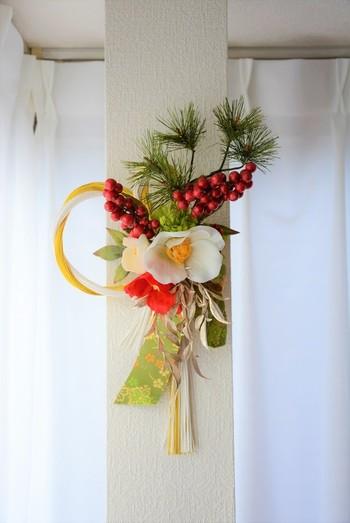 椿、南天、松、黄緑の菊などの縁起物に西陣織りのリボンが和のテイストです。1年の幸せを願ったお正月飾りです。