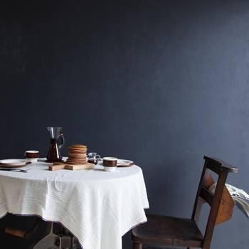 ダークカラーの家具と壁に映える真っ白いテーブルクロス。明・暗の対比がとても美しく、まるで一枚の絵画のような世界。日常を切り取った自然体の風景でありながら、独特の詩的な雰囲気に引き込まれてしまいます。