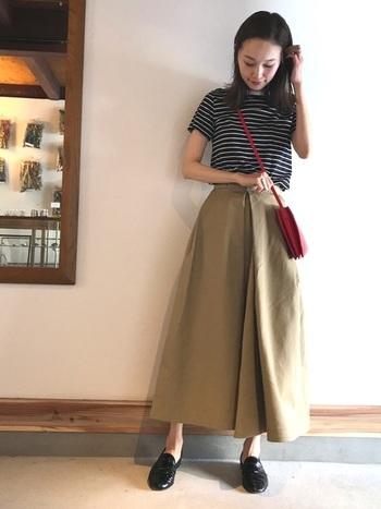 チノ素材のフレアスカートは、ローファーでクラシカルな雰囲気に。赤のショルダーバッグで重心を上にもっていくのがメリハリをつけるポイントです。