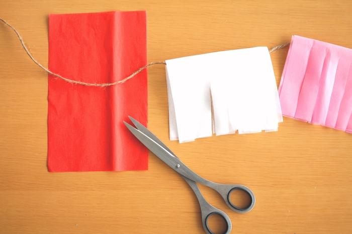赤や白など、数色のお花紙を用意しましょう。一枚のお花紙の中心にボンドで紐を接着して、二つ折りに挟み込みます。いくつか紐に下げたら、紙同士を重ねて縦に切れ込みを入れましょう。 今回は、各色ごとに二枚のお花紙を使ってボリュームをだしてみました。