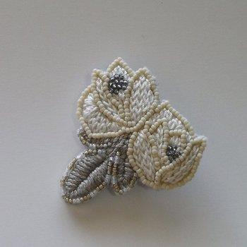 糸とビーズの繊細なバラのブローチ。自己主張の激しくない上品なカラーで、さまざまな服に合わせやすいのがポイントです。