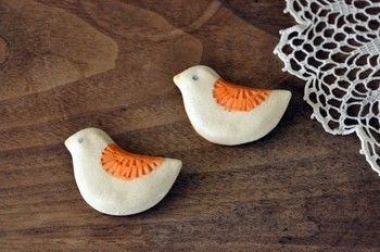 オレンジがアクセントになった小鳥のブローチ。陶器でも軽めに作られており、取り入れやすいデザインになっています。服だけでなく、帽子やバックにもおすすめです。