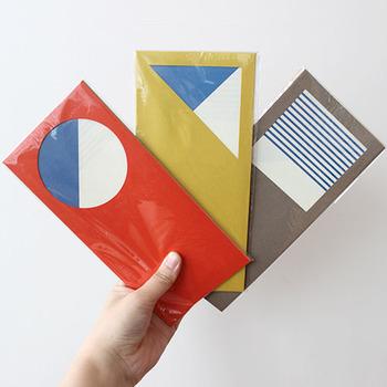 封筒の窓から見える青と白が爽やかで素敵。  中には幾何学模様の紙が3枚ついていて、紙の折り方と封筒に入れる向きによって、窓から見える模様が変わるんです♪ なんと1つのセットで9パターンの組み合わせが楽しめるので毎回折り方を変えてみるのもおすすめです。