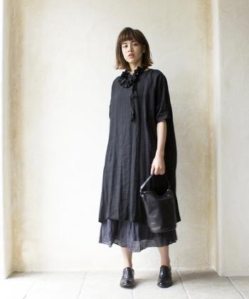 ラリエットがアクセントになった黒のブラックリネンのワンピース。インナーに合わせたチャコールグレーのギャザースカートでニュアンスを加えて。