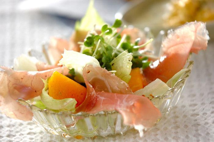 見た目にもおしゃれな柿と生ハムのサラダ。生ハムの塩味と柿の甘みが絶妙なバランス。仕上げにオリーブオイルと白ワインビネガーで作ったドレッシングをかけて。おもてなしにも良さそうです。