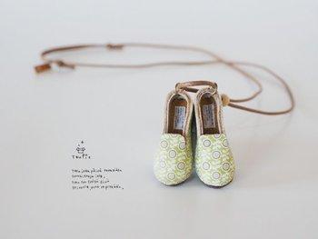 本革製の小さい靴がついたネックレス。花柄のテキスタイルはオリジナルだそうで、麻布の中敷やタグまで細かく作り込まれています。靴は長さ4cmと手頃なサイズ。ネックレスとしてのしっかりとした存在感があります。
