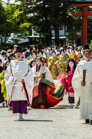 【画像は、平安期から続く、京都三大祭の一つ「葵祭(正式名称:賀茂祭)」。葵を飾った平安装束を纏った人物たちは総勢500名にも及び、行列は時代絵巻のような典雅な眺め。】