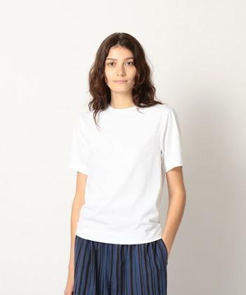 後ろがラグラン、前がふつうの袖になった肩まわりがゆったりのスプリットラグランスリーブのクルーネック白Tシャツは、エフォートレスな着こなしに。