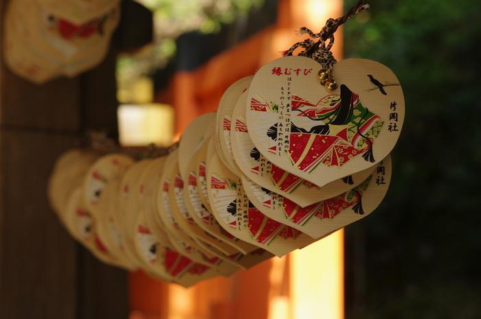 """「片岡社」は、上賀茂神社の御祭神「賀茂別雷大神」の母である「玉依姫(タマヨリヒメ)」を祀った上賀茂神社の第一摂社。縁結び、恋愛成就の御利益があることで良く知られ、紫式部が何度もここに参拝したことでも有名な社です。 片岡社では、源氏物語の絵柄のついた絵馬に願いを書き込んで奉納することが出来ます。一見ハート型に見える絵馬ですが、賀茂神社の神紋""""双葉葵""""を模しています。"""