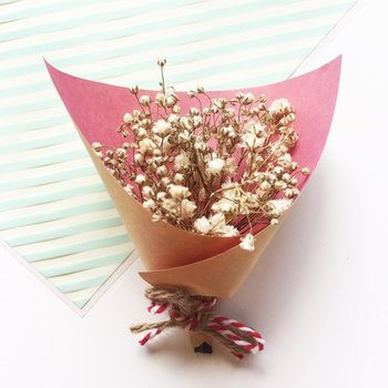 手の平に乗るぐらい小さな花束のギフトは、ちょっとした気持ちを伝えるのにおすすめです。真っ白なお花がピンクのラッピングペーパーに映えてとてもキレイ。  折り紙ぐらい小さな紙でも包めるので、誰でも簡単にできますよ。