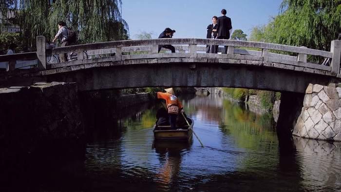 【倉敷は、豊かな自然環境を背景に、農産物だけでなく、水運にも恵まれて栄えた町。現在でも、中国・四国地方の交通の要衝に変わりはありません。画像は、倉敷川に架かる「中橋」。緩やかな反りは、航行を配慮したためと伝えられています。】