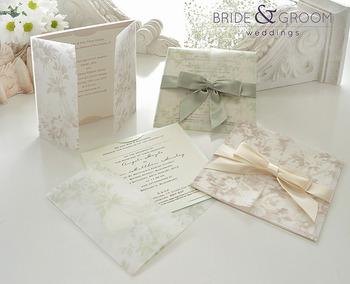 色のトーンを抑えたシンプルな招待状。花柄の封筒、アースカラーのリボンでナチュラルな印象に。