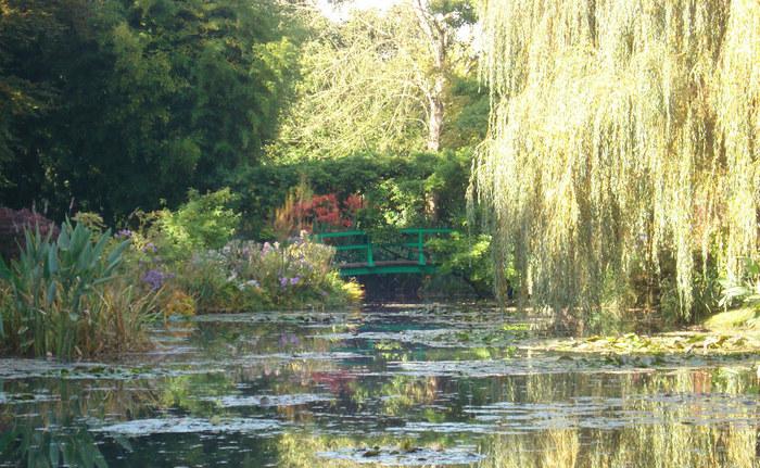 """浮世絵に出てくるような日本風の太鼓橋はモネの庭でも人気のスポット。家と同じ緑色が庭の雰囲気にぴったり。橋の上には藤棚が配されています。フランスでは""""日本橋""""と呼ばれているそうですよ。  当時ヨーロッパには異国風のもの、特にジャポニスムと呼ばれる日本の風物のブームが起こっていました。モネは浮世絵のコレクターでもあり、こちらの太鼓橋(日本橋)だけでなく、構図やモチーフにもその影響を見ることができます。邸宅内では浮世絵が飾られた居間も見られます。"""