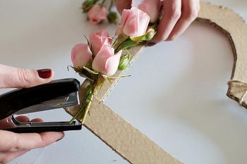 2.バラを短めに切って4輪ほどを麻紐でまとめて、ハートの段ボールにホッチキスでバラを留めていきます。