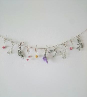 大きな花束じゃなくても、散歩の途中で見つけた小さな花やミニブーケからでも作れます。長さやサイズ感を揃えてたくさん連ねれば素敵なガーランドに。紐の端をマスキングテープで止めればピンを刺せない壁にもOK。