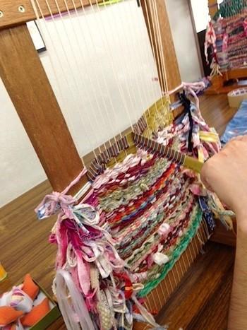 裂いた布と紐を交互に織っていく「裂き織り」は、基本的に織り機を使いますが、段ボールで手作りの織り機を作ることもできるそう。使いたい布を裂き、途切れる事のない一本の紐状にします。そして「経糸」と呼ばれる縦の糸に、裂いた布と紐を交互に重ねていきます。
