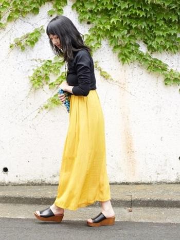色鮮やかなロング丈のスカートにブラックのトップスとサボサンダルで引き締めて。ふわっと風になびく黄色のスカートを主役にしたおしゃれ上級者コーデです。