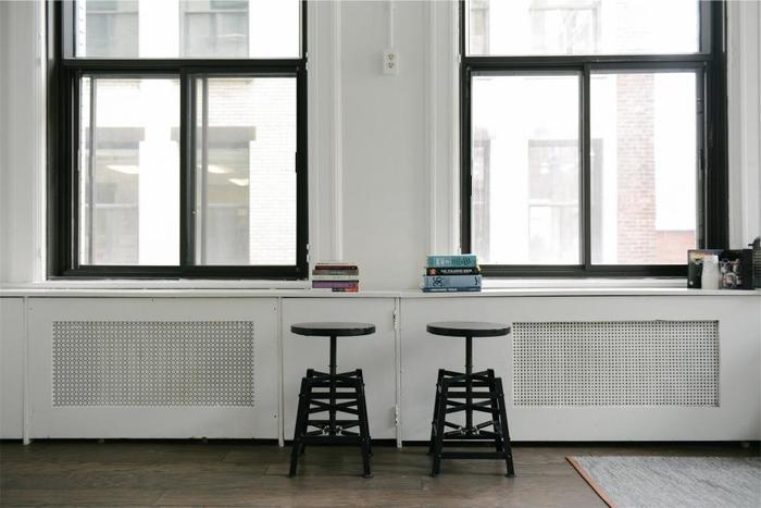 スツールは座るだけでなく、部屋のオブジェとして、小さなテーブルとして、いろいろな使い方ができます。形の美しい黒のスツールを窓のフレームに合わせて左右対称、そしてグラフィカルに配置した絵になる空間です。