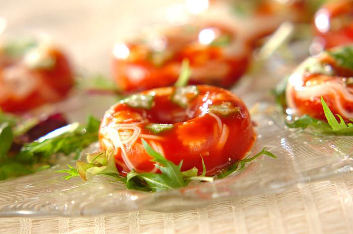 涼しげに盛り付けられたこちらのお料理は、そうめんをトマト寒天で固めたものなんです。暑い日のオードブルに良さそうですよね。  顆粒スープの素で味をつけるので、トマトジュースは無塩を使いましょう。トマト寒天からうっすら透ける白いそうめんとオクラの緑がキレイです。七夕パーティーに作ったら、盛り上がりそうですね。