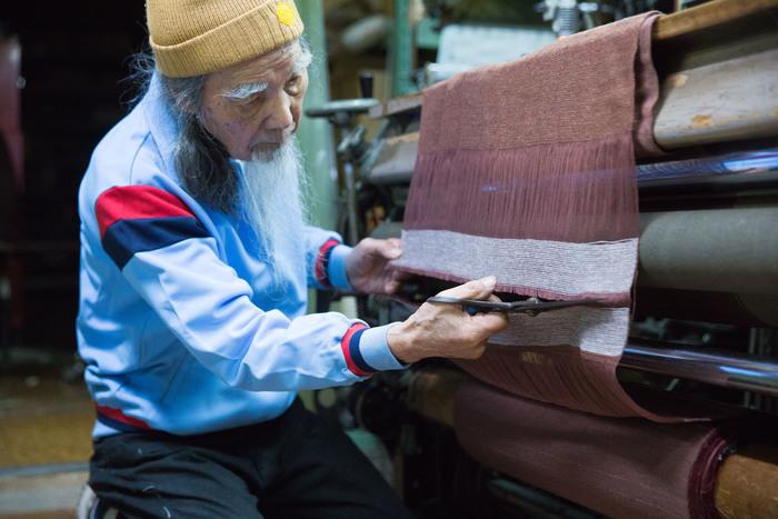 工場にて。2017年の秋冬商品に使うサンプル布を織り機からカットする場面。こちらの織機は、昭和20年代ごろから使っているそう
