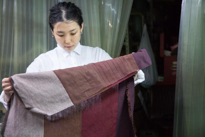 工場で、織り上がったサンプルを真剣に確認する瀬谷さん