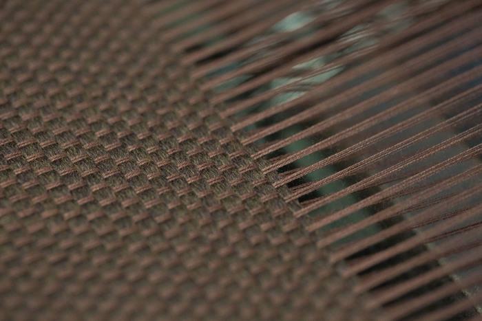 アナログな織り機によって、経糸と緯糸が空気をはらみながら合わさっていきます。機械で織るとはいいつつも、よい布が織れているかの確認や作業など、人の「目」や「手」が重要です