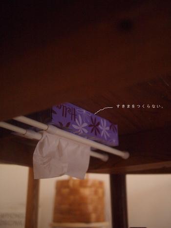 ダイニングテーブルに置いたボックスティッシュ。生活感があってイマイチですが、かといってないと困りますよね。  そこで考えたのが「テーブルの裏に収納する」というアイデア。突っ張り棒を渡した上にボックスティッシュを置きました。ポイントは、取り出し口を下に向けること。こうすることで、覗かなくても手を伸ばすだけでティッシュが取り出せます。  天板とボックスティッシュの間に隙間を作らないようにすると、普段は見えないのもポイントです。