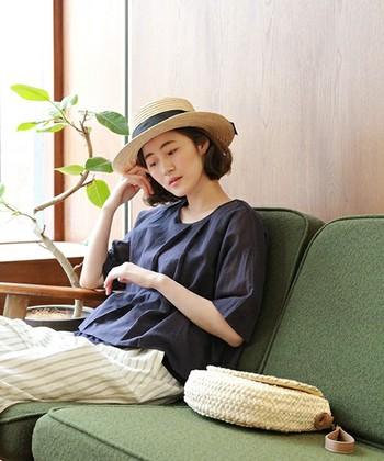 カフェのようなリラックスした空間にもしっくり溶け込むラフィア素材のカンカン帽で、夏気分アップ!落ち着いた紺のブラウス+白のストライプパンツが知的で大人な女性らしさを引き立ててくれます。