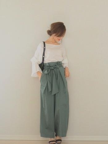 落ち着いたグリーンのパンツとフリル袖の白いブラウスでおしゃれなママに♪さりげないまとめ髪も素敵ですね。