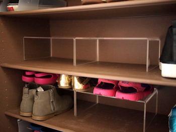 玄関の靴収納をすっきり見せるために、透明のアクリル仕切りを使いました。仕切り同士がぴったりくっつくので、余計な隙間を作ることなく靴が収納できます。  子どもの靴を平らに並べるとスペースをとってしまうことが多いので、このように2段に分けて収納するとたくさんしまえて便利ですね。
