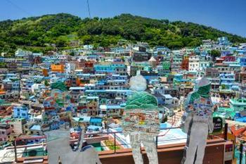 韓国の釜山にある「甘川洞文化村」は現代アートの街。山肌に沿って立ち並ぶ家屋はカラフルに塗られ、入り組んだ路地には数々のアート作品があります。  写真は人型のパネルに村の絵が描かれた「甘川と一つになる」というアート。