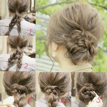 髪を一つ結びにしたら、毛先を2つに分けて2本の三つ編みを作ります。 左側を右側の三つ編みの下をぐぐらせ、反時計まわりに巻きつけてピンで固定します(右側は時計まわりに)。 全体を少し崩せば、素敵なアップヘアスタイルの完成です♪