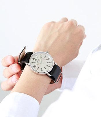 黒ベルトの大きな腕時計は、バングルをしているような感覚で、手首にさり気なくインパクトを与えます。コーディネートはシンプルにまとめ、腕時計を引き立てる着こなしで。