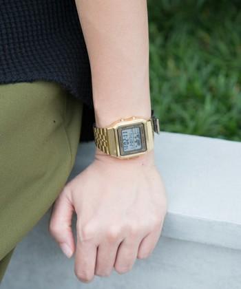 ボーイッシュなゴールドのデジタル腕時計。あえてきれいめなカジュアルスタイルに合わせて遊び心を加えて。
