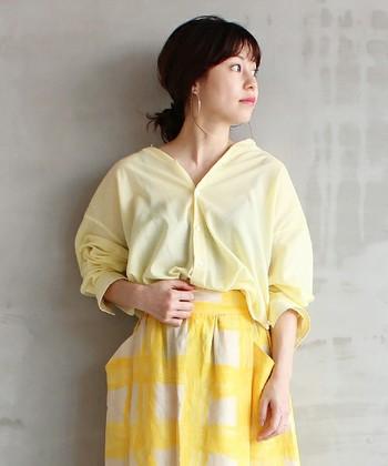レモンカラーのビッグシルエットのとろみシャツ。ふんわりやわらかな印象で、ぐっと抜き襟にして着ると今年らしさ満点です。