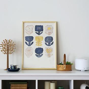 もっと手軽に模様替えをしたい方にオススメなのが、ポスター類です。 こちらは愛らしい花の絵柄が素敵な図案ポスター。白×イエローの優しい色合いにシックな藍色でアクセント。お部屋に飾るだけでほんわかと柔らかな雰囲気に。