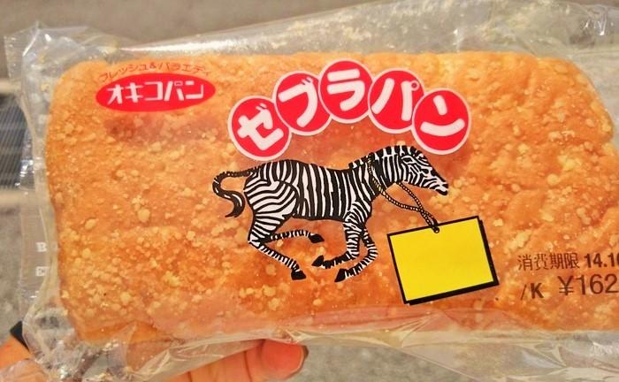 """パンを持つのは男性の手。目を見張る大きさです★沖縄では、体育会系の高校生の圧倒的な支持を得ているとか。 """"黒糖フラワーペーストを折り込み、ピーナツクリームをサンドしたボリュームのあるパンです。軽くトーストして表面に少し焼き色をつけて中のクリームが少し溶けるぐらいでお召し上がりいただくことをおすすめします""""と製造元の「オキコパン」。発売は1980年代。"""