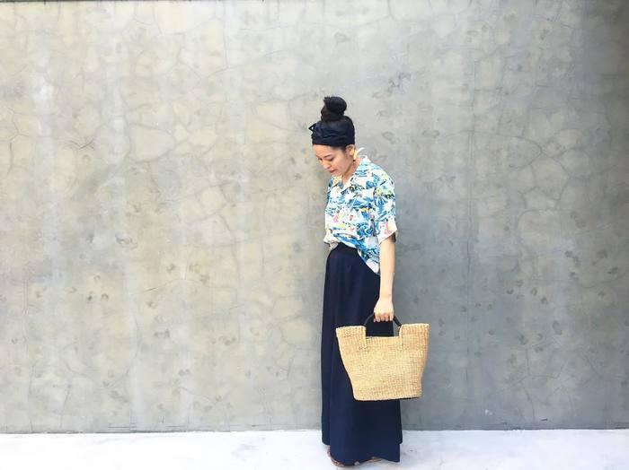 マキシ丈のブラックロングスカートには、派手柄のシャツを合わせて、リゾートを髣髴させる着こなしで。カゴバックとの相性も抜群ですね。