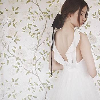"""""""後ろ肩紐のフリルが花嫁のキモチに寄り添う一着はスペインから"""" ロングのリボンがアクセントに。"""
