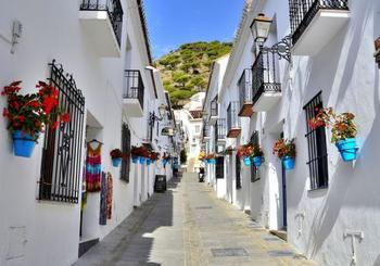 スペイン南部のアンダルシア地方にある「ミハス」。太陽の日差しが燦々と降り注ぎ、青い空に白壁が美しい、いかにもスペインらしい景観が楽しめます。  坂が多く入り組んだ路地には、沢山の花かごが飾られていて華やか。黒色の鉄細工の窓枠やバルコニーが白壁をいっそう引き立てています。