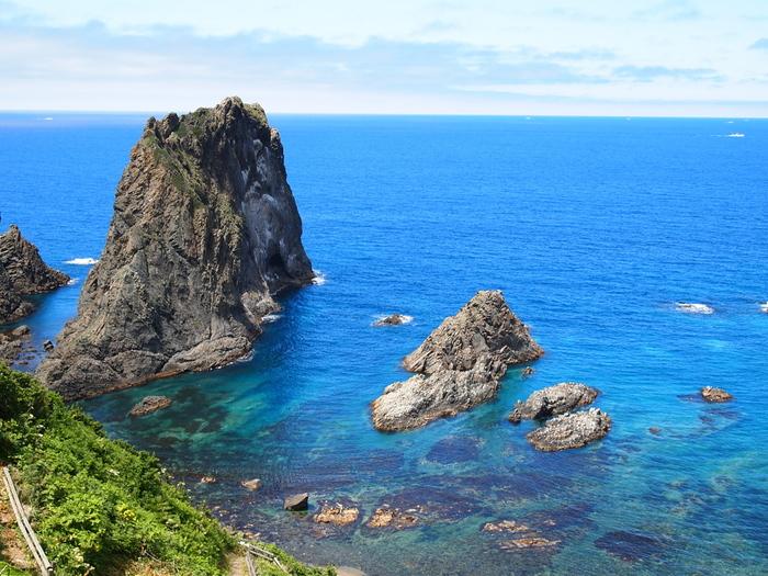 島武意海岸は、「日本の渚100選」にも選定されており、積丹町を代表する景勝地の一つです。遥か彼方に見える水平線まで続くサファイヤ色に輝く海は、抜群の透明度で展望台から海底が見えるほどです。