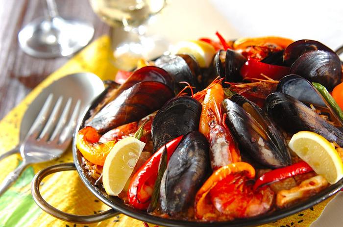 """「パエリア」は、スペインの米どころバレンシア地方が発祥で、パエリアとは""""フライパン""""の意味。現在のパエリアは魚介類を具材にしたものが一般的ですが、バレンシアパエリアは猟師が獲物を米といっしょに煮込んだことに始まっており、具はうさぎ肉や鶏、カタツムリなどを使います。"""