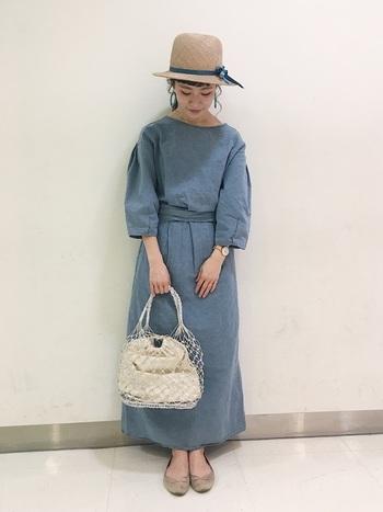 濃いベージュ系の麦わら帽子は、全体を大人っぽい印象。麦わら帽子のリボンとワンピースのカラーを合わせることで、統一感のある着こなしに。