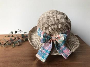 大きなリバティ柄のリボンがガーリーな麦わら帽子。シンプルなワンピースや夏らしいホワイトコーデに合わせると、ぐっと素敵になりそうですね。