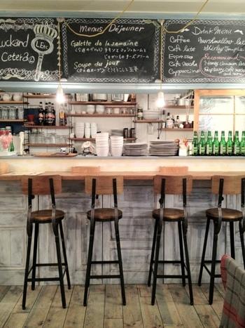 白とレトロな木目を基調としたカフェは、シャービーでアンティークな雰囲気。人気店のため、ランチタイムにはほぼ満席になります。お料理を作る様子が見られるカウンターは、特等席♪