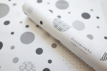 グラフィカルなドット模様がおしゃれなラッピングペーパー。表と裏が異なる肌触りのハトロン紙を使用しています。好きな大きさにカットして、ブックカバーなどの小物使いにもおすすめです。