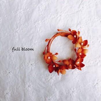 白い布を、大人っぽいスモーキーオレンジに色付けして作った上品なブローチ。シンプルなお洋服に、差し色としてきかせたいですね。